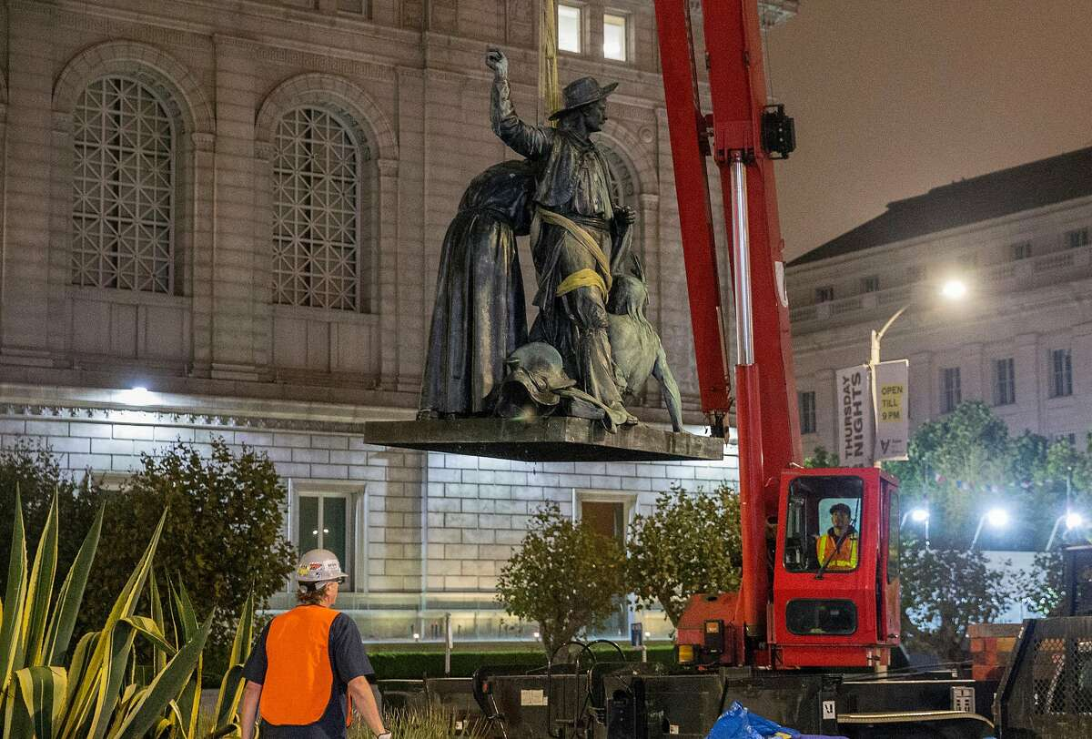 The controversial 'Early Days' statue, one of five statues that make up the Pioneer Monument, is lifted from its platform as it is removed in San Francisco Calif. Friday, Sept. 14, 2018.