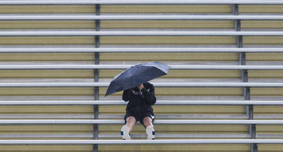PHOTOS: Flooding photos from Tropical Depression Imelda A Montgomery fan sits in the rain before a non-district high school football game, Thursday, Sept. 13, 2018, in Montgomery. >>>Staff photos from the effects of Imelda on Thursday, Sept. 19, 2019 ... Photo: Jason Fochtman/Staff Photographer