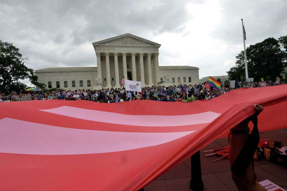People wave a giant equality flag in celebration outside the Supreme Court in Washington, DC on June 26, 2015, after its historic decision on gay marriage. The US Supreme Court ruled Friday that gay marriage is a nationwide right, a landmark decision in one of the most keenly awaited announcements in decades and sparking scenes of jubilation. Photo: MLADEN ANTONOV / AFP / Getty Images File / AFP