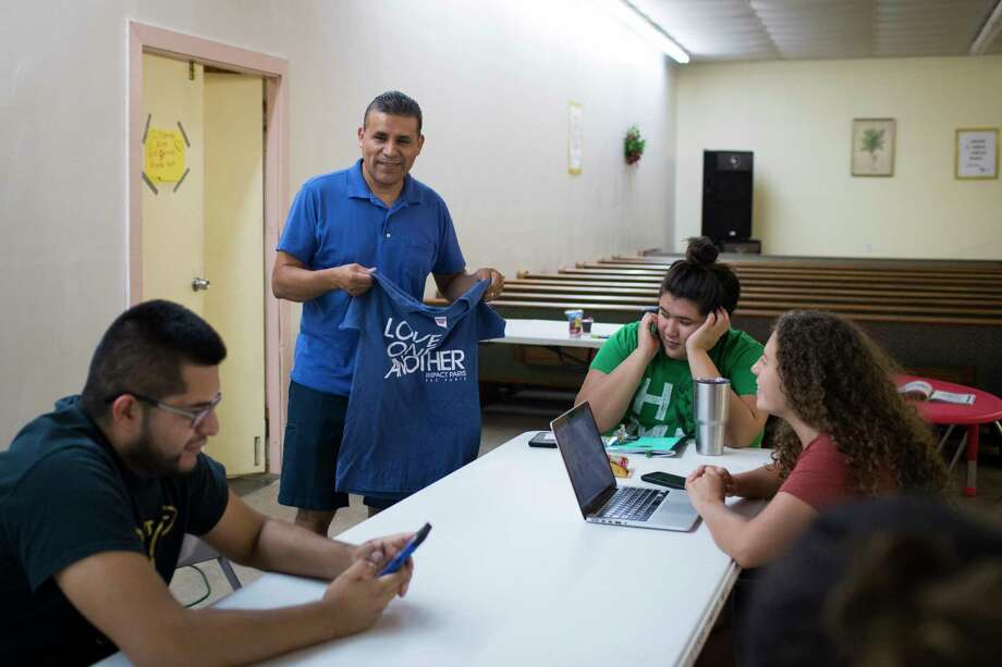 "Pastor Beto Prado, who has been helping families affected by the ICE raid, looks at a t-shirt that says ""Love One Another"" before a planning meeting, Thursday, Sept. 6, 2018, in Paris. Photo: Marie D. De Jesús, Staff Photographer / © 2018 Houston Chronicle"