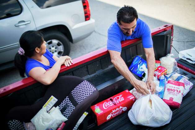 Maria del Carmen Castrejon, 37, got groceries with the help of Pastor Moises Navarrete, Wednesday, Sept. 5, 2018, in Paris. Castrejon lost her job after federal agents raided the Load Trail factory.  Photo: Marie D. De Jesús, Staff Photographer / © 2018 Houston Chronicle