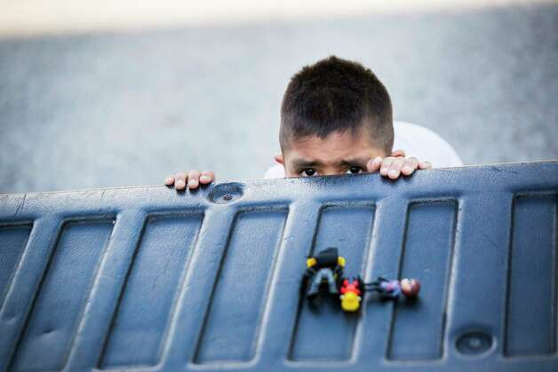 Misael Arenas, 4, hides behind the back of his mother's truck in Paris, Wednesday, Sept. 5, 2018.  Photo: Marie D. De Jesús, Staff Photographer / © 2018 Houston Chronicle
