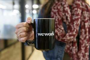 A woman displays a WeWork branded coffee mug for a photograph at the Embarcadero WeWork offices in San Francisco on Oct. 19, 2017.