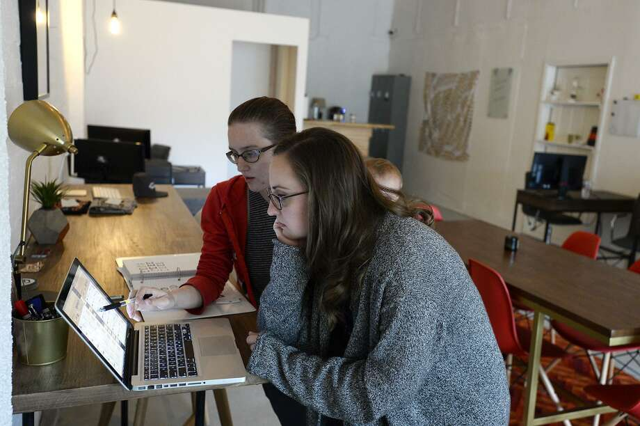A man and woman share a co-working space. Employment trends show a greater number of people are unable to find full-time employment and rely on freelance work to get by, according to the Middlesex County United Way. Photo: File Photo / ©2017 The Beaumont Enterprise/Ryan Pelham