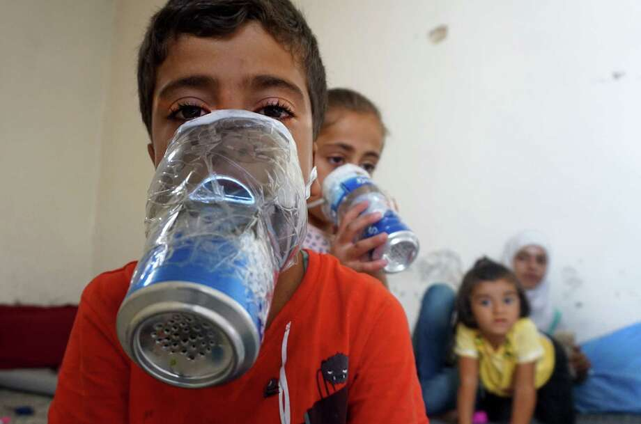 TOPSHOT - Children try improvised gas masks in their home in Binnish in Syria's rebel-held northern Idlib province as part of preparations for any upcoming raids on September 12, 2018. - The Syrian regime and its Russian ally are threatening an offensive to retake the northwestern province of Idlib, Syria's last rebel bastion. (Photo by Muhammad HAJ KADOUR / AFP)MUHAMMAD HAJ KADOUR/AFP/Getty Images Photo: MUHAMMAD HAJ KADOUR / AFP or licensors