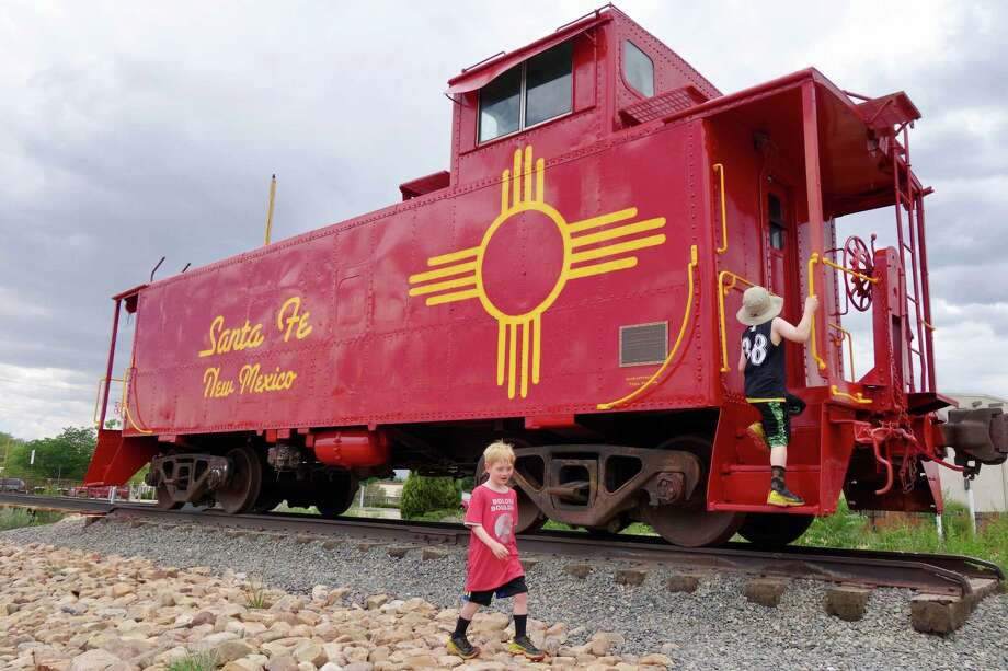 The author's sons explore an old railcar secured on the tracks at the Railyard, a popular Santa Fe gathering spot. Photo: Photo For The Washington Post By Rachel Walker / Rachel Walker