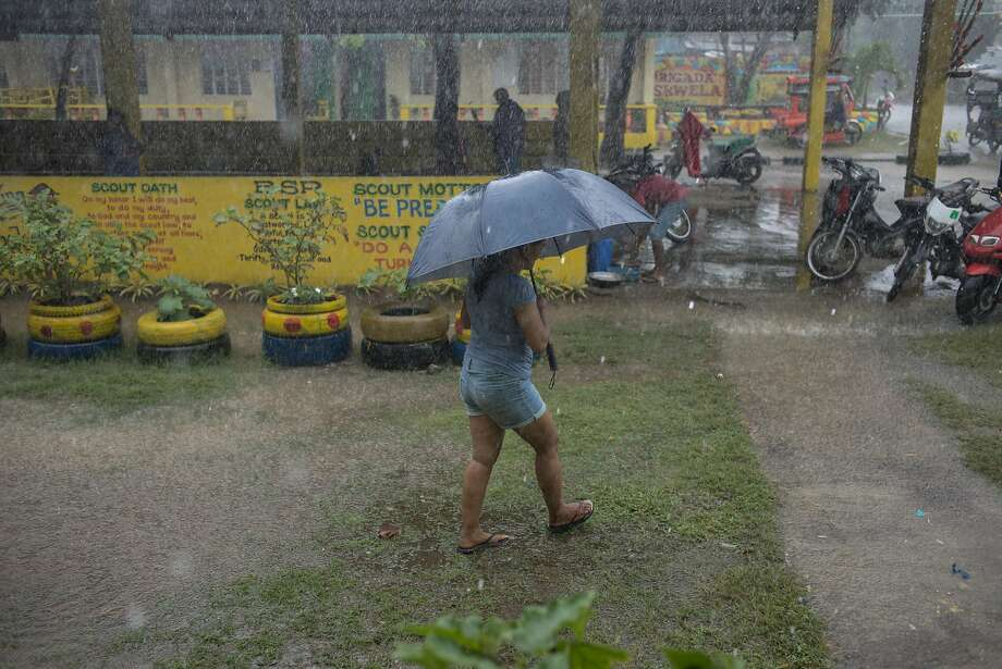 A woman shelters under an umbrella during heavy rainfall outside the temporary evacuation center at Balzain East Elementary School ahead of Typhoon Mangkhut's arrival in Tuguegarao, Cagayan province, the Philippines, on Friday, Sept. 14, 2018. Philippines authorities are evacuating thousands of people in the path of Super Typhoon Mangkhut to safer grounds hours before the cyclone slams into the country's northern provinces. Photographer: Carlo Gabuco/Bloomberg Photo: Carlo Gabuco / Bloomberg