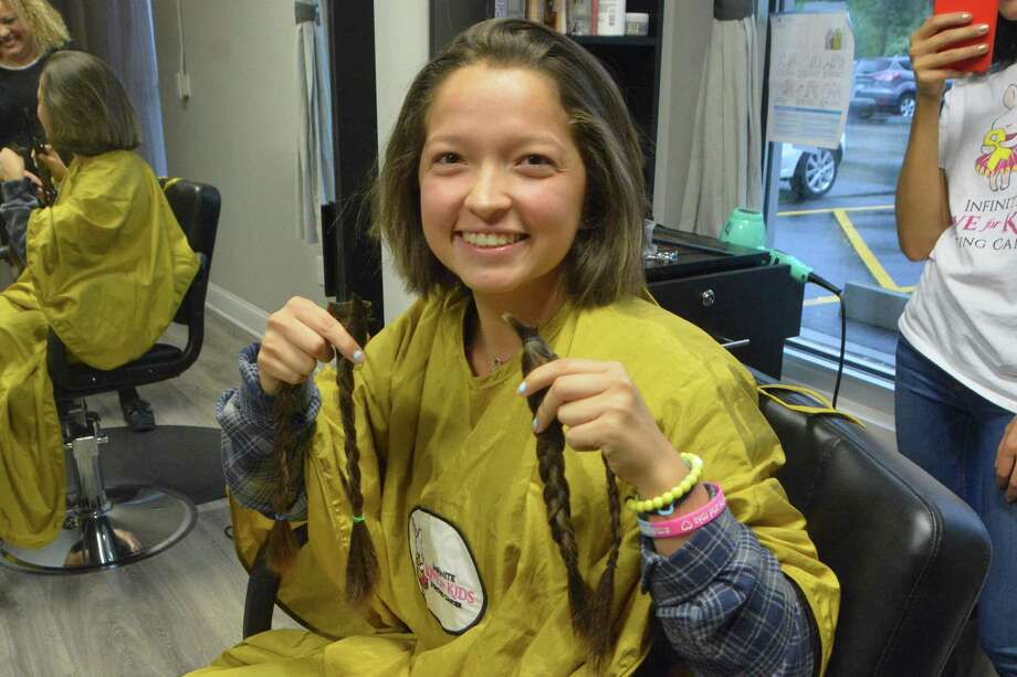 Jess Salgado, a student at Trumbull (Conn.) High School, holds up what used to be her ponytails. They were cut off as part of a fundraiser for pediatric cancer research, and the hair will be used for wigs for child cancer patients. Photo: Contributed Ohoto