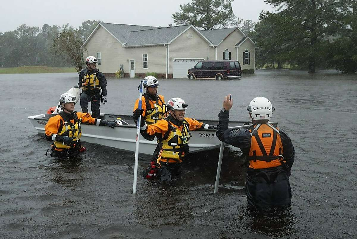 Members of the FEMA Urban Search and Rescue Task Force 4 from Oakland, Calif., search a flooded neighborhood for evacuees during Hurricane Florence September 14, 2018 in Fairfield Harbour, North Carolina.