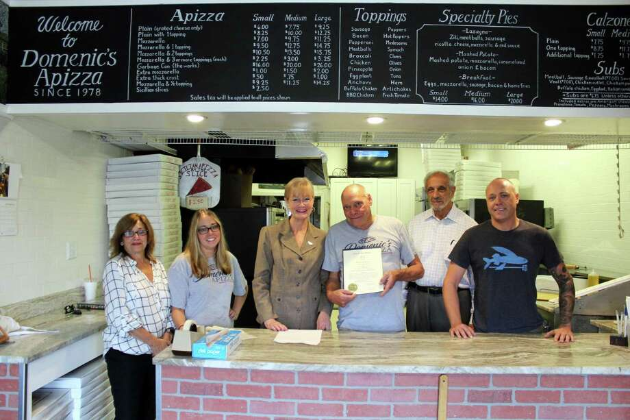 """CELEBRATING 40 YEARS: Domenic's Apizza owner Domenic Giannotti, center, receives a citation for 40 years in business from Mayor Nancy R. Rossi, third from left, on Sept. 12 at 18 Ocean Ave. On hand to mark the occasion are, from left, City Clerk Deborah Collins; Giannotti's daughter, Kyle; mayoral Executive Assistant Lou Esposito; and Giannotti's son, Domenic. Rossi recognized Giannotti, a longtime city resident who has been making pizzas and grinders for takeout in the Baybrook Shopping Center since 1978, for """"the celebration of your 40th anniversary and successful career in the pizzeria business."""" The  pizzeria is open Sunday, 3-9 p.m.; Tuesday-Thursday, 11 a.m.-9 p.m.; and Friday-Saturday, 11 a.m.-10 p.m. Photo: Contributed Photo / Michael P. Walsh - City Of West Haven"""