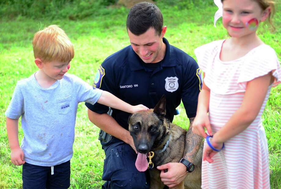 Colin Delarosa, 3, of Litchfield, pets Officer Steve Santoro's K9 Logan as he and his sister Aubrie, 6, pose for photos during the Stratford Police K9 Unit's annual fundraiser at Riverview Bistro in Stratford, Conn. on Saturday Sept. 1, 2018. The unit held hourly demontrations to show off the dog's skills at finding evidence, leaping over walls and playing with their toys as a reward. The department also had many of its special vehicles on display, like a Kiowa helicopter, its marine unit as well as some vehicles from the fire and EMT departments. Photo: Christian Abraham / Hearst Connecticut Media / Connecticut Post