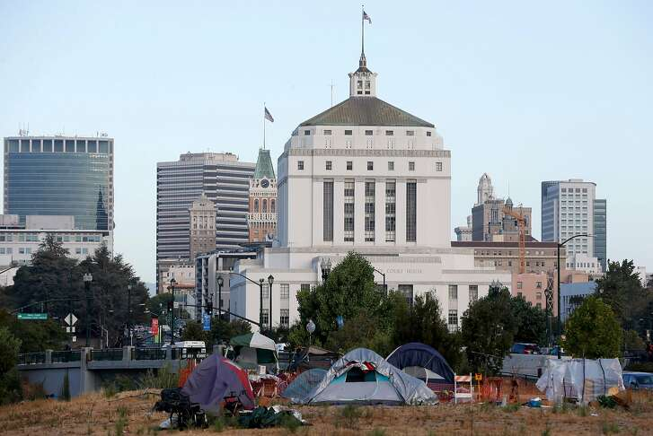 A homeless encampment occupies a vacant parcel slated for development at Lake Merritt Boulevard and East 12th Street near the Kaiser Convention Center and county courthouse (background) in Oakland, Calif. on Thursday, Sept. 13, 2018.
