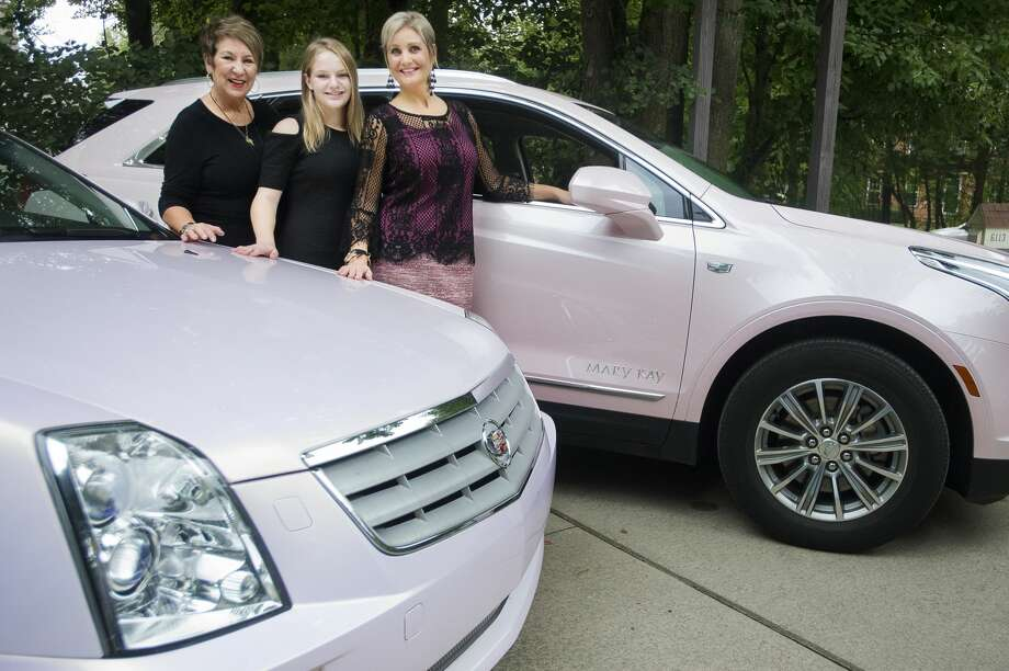 From left, Judy Kawiecki, her granddaughter Brynn Hansen and daughter Lisa Hansen pose for a portrait between pink Cadillacs owned by Kawiecki and Hansen, both Mary Kay consultants, on Thursday in Midland. Kawiecki and her husband John drove Hansen's vehicle in a funeral procession for Aretha Franklin on Aug. 31 in Detroit. (Katy Kildee/kkildee@mdn.net) Photo: (Katy Kildee/kkildee@mdn.net)