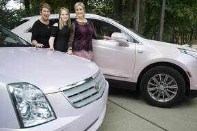 From left, Judy Kawiecki, her granddaughter Brynn Hansen and daughter Lisa Hansen pose for a portrait between pink Cadillacs owned by Kawiecki and Hansen, both Mary Kay consultants, on Thursday in Midland. Kawiecki and her husband John drove Hansen's vehicle in a funeral procession for Aretha Franklin on Aug. 31 in Detroit. (Katy Kildee/kkildee@mdn.net)