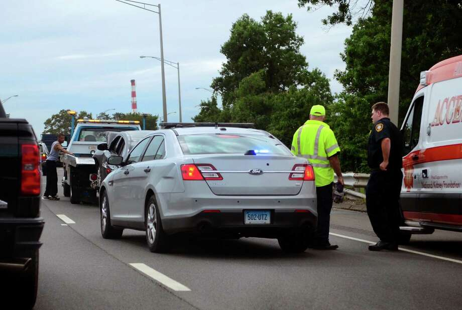 Crews work to remove a vehicle involved in a crash just past exit 30 along I-95 southbound in Stratford, Conn., on Friday Sept. 14, 2018. Minor injuries were reported in the accident which closed the right lane of traffic. Photo: Christian Abraham / Hearst Connecticut Media / Connecticut Post