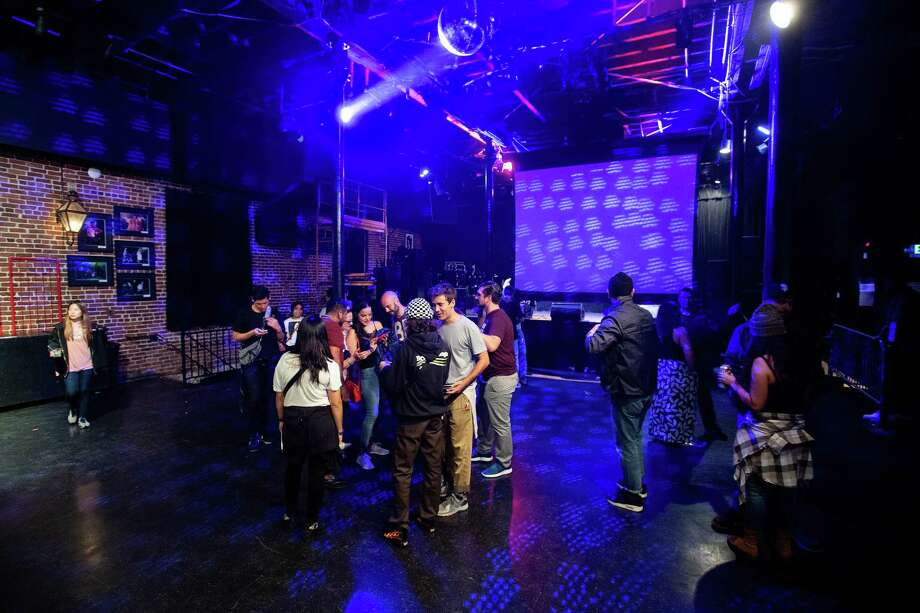 Concert-goers look at photos after a Bad Gyal performance at Slim's on Thursday, Sept. 13, 2018. Photo: Noah Berger / Special To The Chronicle / online_yes