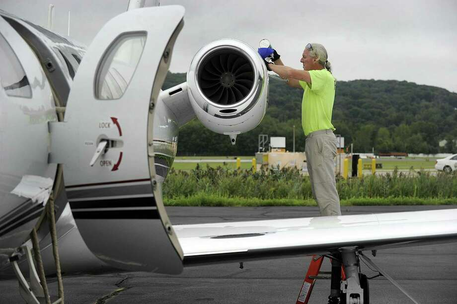 Above, Colin Mannion manager of ground support services for Reliant Air, adds fuel oil to a Cessna Citation in preparation for a scheduled flight out of Danbury Airport Tuesday. At top, the Cessna takes off from the airport after fueling. Photo: Carol Kaliff / Hearst Connecticut Media / The News-Times