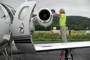 Above, Colin Mannion manager of ground support services for Reliant Air, adds fuel oil to a Cessna Citation in preparation for a scheduled flight out of Danbury Airport Tuesday. At top, the Cessna takes off from the airport after fueling.