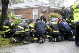 Firefighters and rescue crew pray in front of a home after removing a resident trapped inside, due to a fallen tree, during Hurricane Florence in Wilmington, North Carolina, U.S., on Friday, Sept. 14, 2018. Hurricane Florence is delivering driving wind, pelting rain and torrential flooding to North Carolina, killing at least two people as it grinds through the region. Photographer: Alex Wroblewski/Bloomberg