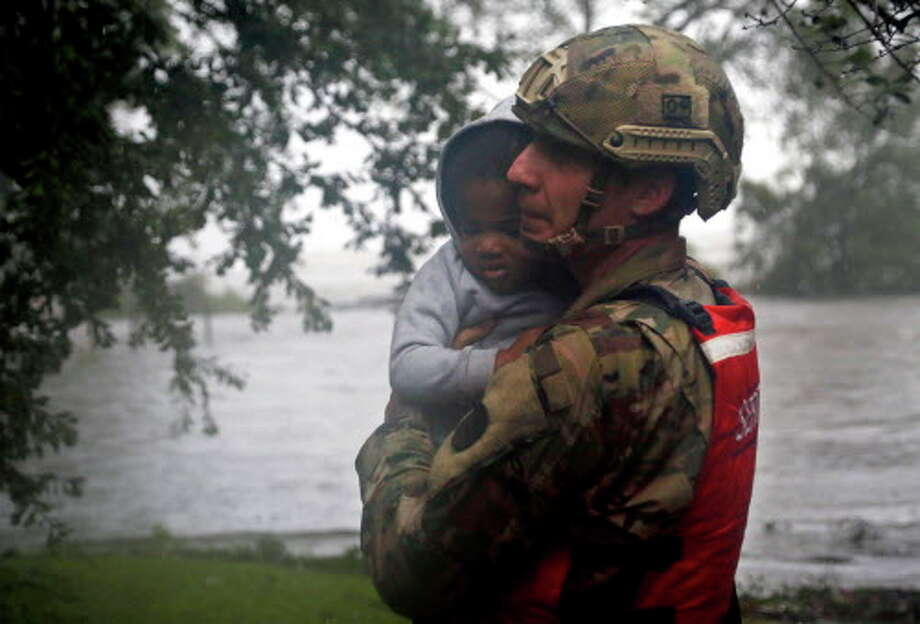 Rescue team member Sgt. Nick Muhar, from the North Carolina National Guard 1/120th battalion, evacuates a young child as the rising floodwaters from Hurricane Florence threatens his home in New Bern, N.C., on Friday, Sept. 14, 2018.  Photo: Chris Seward, Associated Press / Copyright 2018 The Associated Press. All rights reserved