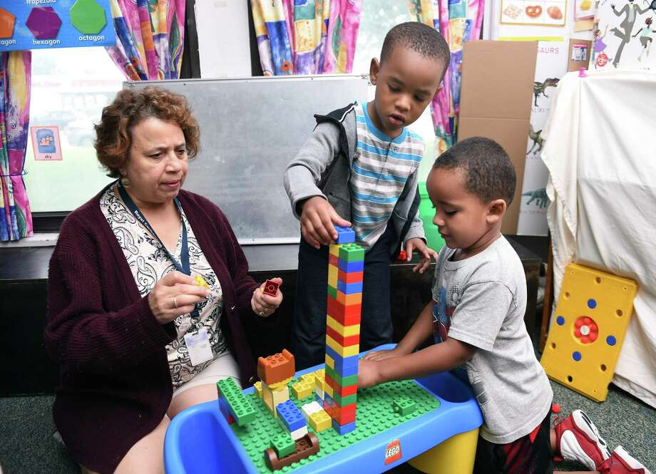 From left, Sleeping Giant Day Care Assistant Director Sharon Fuoco builds a Lego tower with Zephaniah Thomas, 4, and Avion Bowman, 4. Photo: Arnold Gold / Hearst Connecticut Media / New Haven Register