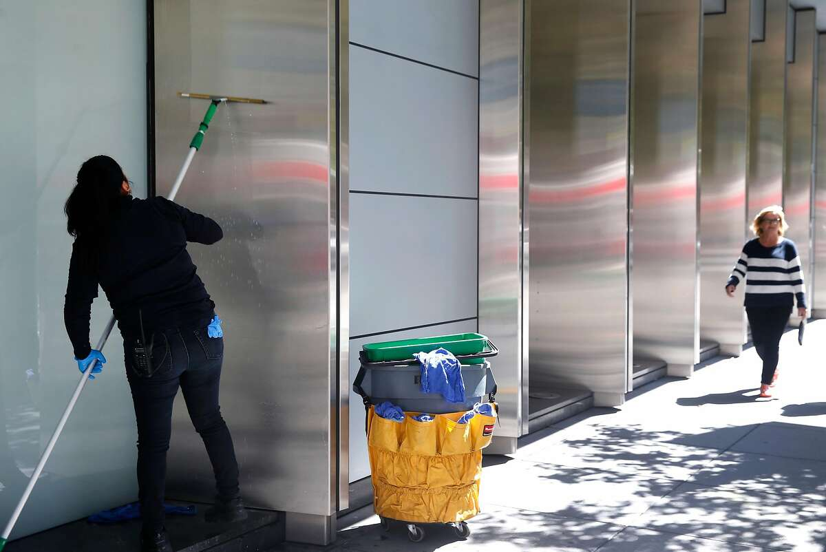 A woman washes the base of the Millennium Tower in San Francisco, Calif. on Thursday, Sept. 13, 2018. City building inspectors ordered the building's operators to erect scaffolding above the sidewalk surrounding the building after a window cracked above Mission Street.