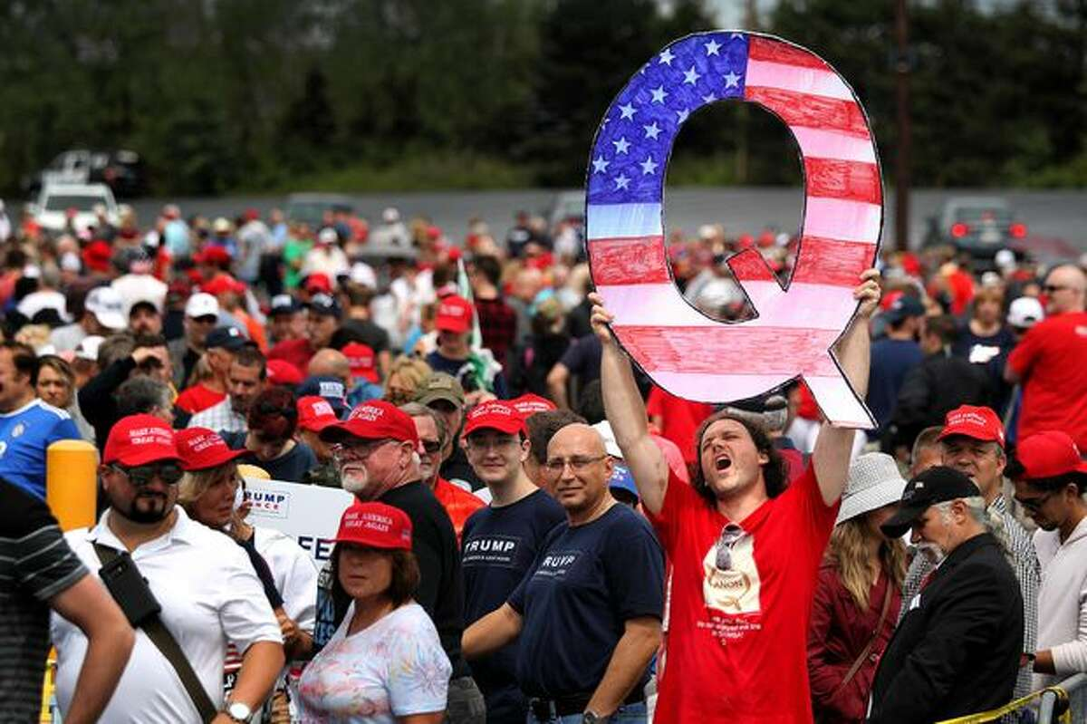 """A Trump supporter holds up a Q sign on Aug. 2 at the Mohegan Sun Arena in Wilkes Barre, Pa. """"Q"""" represents QAnon, a conspiracy theory group."""