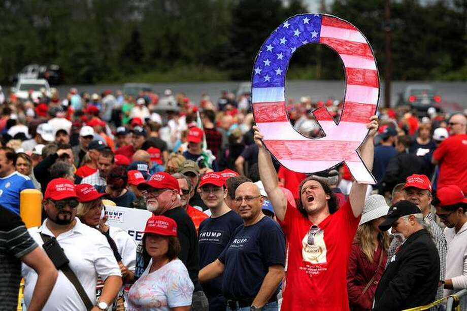 "A Trump supporter holds up a Q sign on Aug. 2 at the Mohegan Sun Arena in Wilkes Barre, Pa. ""Q"" represents QAnon, a conspiracy theory group. Photo: Rick Loomis/Getty Images"