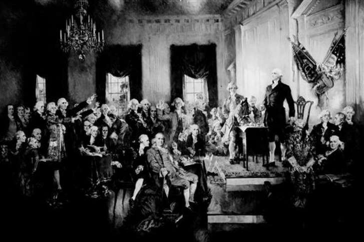 This photo provided by the Library of Congress shows a painting by Howard Chandler Christy on display in the U.S. Capitol of George Washington presiding at the signing of the Constitution of the United States in Philadelphia on Sept. 17, 1787. Since then there has been a misunderstanding of the so-called three-fifths compromise.