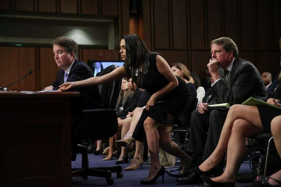 Supreme Court nominee Judge Brett Kavanaugh receives a notes from former law clerk Zina Bash as he testifies before the Senate Judiciary Committee on the third day of his confirmation hearing on Sept. 6. Some leftists on Twitter accused Bash of flashing a white-supremacy sign during the hearings. Photo: Drew Angerer /Getty Images / 2018 Getty Images