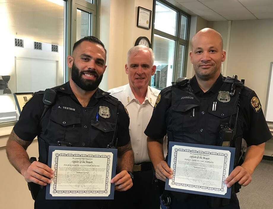 Police Officer Alex Testani, left, and Master Police Officer Carl Johnson, right, receive the Officer of the Month Award from Chief James Heavey, center. Photo: / GPD