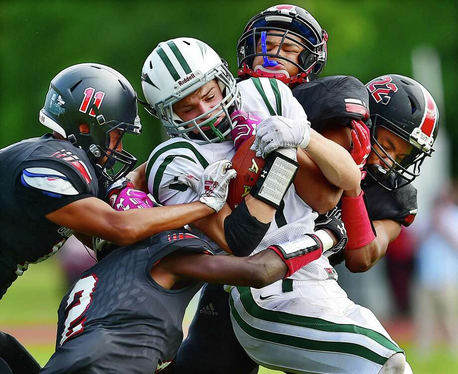 New Milford's Connor Gannon is tackled by Wilbur Cross' Donald Burris (2), Jeremy Martinez (11), Jabez Cubiz (26) and Michael Deleon on Friday in New Haven. Photo: Catherine Avalone / Hearst Connecticut Media / New Haven Register