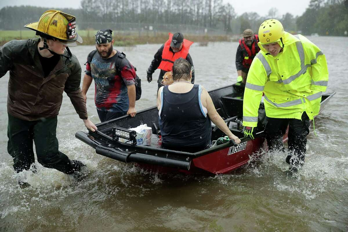 JAMES CITY, NC - SEPTEMBER 14: Rescue workers from Township No. 7 Fire Department and volunteers from the Civilian Crisis Response Team use a boat to rescue a woman and her dog from their flooded home during Hurricane Florence September 14, 2018 in James City, United States. Hurricane Florence made landfall in North Carolina as a Category 1 storm and flooding from the heavy rain is forcing hundreds of people to call for emergency rescues in the area around New Bern, North Carolina, which sits at the confluence of the Nueces and Trent rivers. (Photo by Chip Somodevilla/Getty Images)