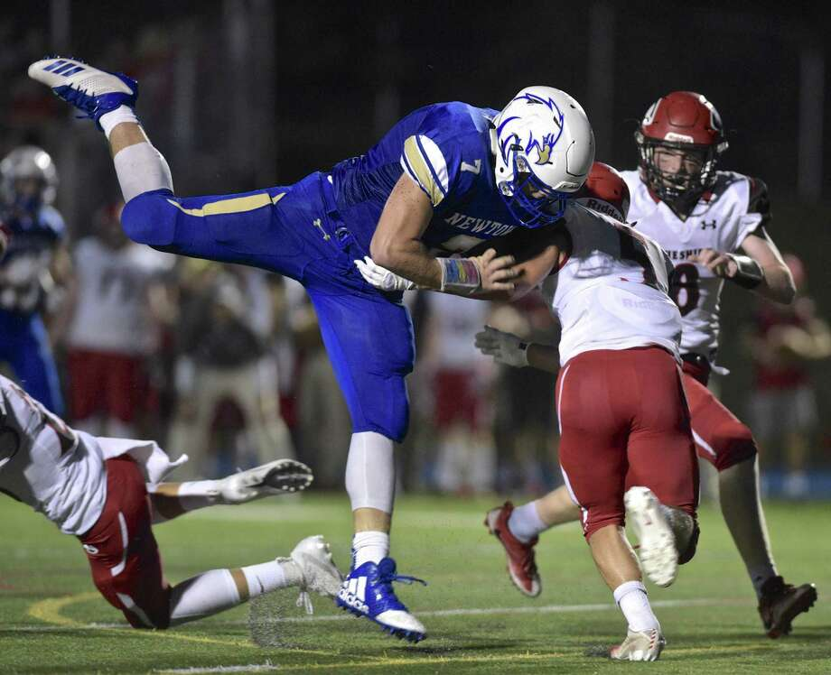 Newtown's Dan Mason (7) is upended and stopped by Cheshire's Alec Frione (5) in the football game between Cheshire and Newtown high schools, Friday night, September 14m 2018, at Newtown High School, in Newtown, Conn. Photo: H John Voorhees III / Hearst Connecticut Media / The News-Times