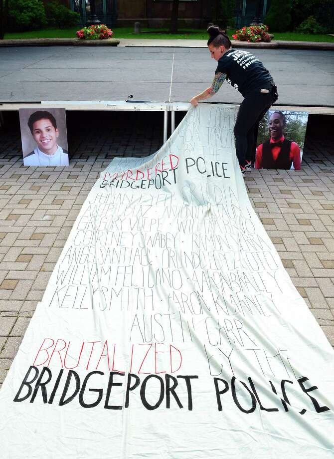 Sarah Pimento, with the Justice for Jayson Coalition, works on securing a banner made for a rally organized by the coallition and Bridgeport Generation Now at McLevy Green in downtown Bridgeport, Conn., on Friday Sept. 14, 2018. Participants remembered Negron, who was killed in a shooting by the Bridgeport Police last May, as well as several others who attendees said were murdered or brutalized by police. Photo: Christian Abraham / Hearst Connecticut Media / Connecticut Post