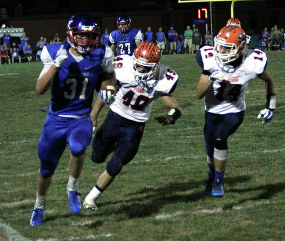 Carlinville wide receiver Kyle Dixon (left) beats Pana defenders Lane Perry and Connor Schmitz down the sideline for a 52-yard TD reception in the first quarter Friday night in Carlinville. Dixon had five TD catches, all in the first half, in the Cavs' 49-12 victory. Photo: Greg Shashack / The Telegraph