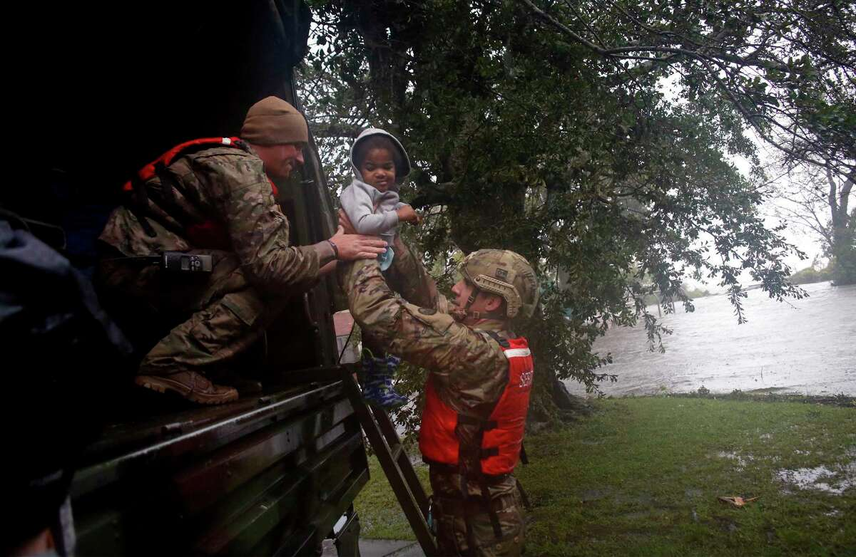 Rescue team members Sgt. Matt Locke, left, and Sgt. Nick Muhar, right, from the North Carolina National Guard 1/120th battalion, evacuates a family as the rising floodwaters from Hurricane Florence threatens their home in New Bern, N.C., on Friday, Sept. 14, 2018. (AP Photo/Chris Seward)