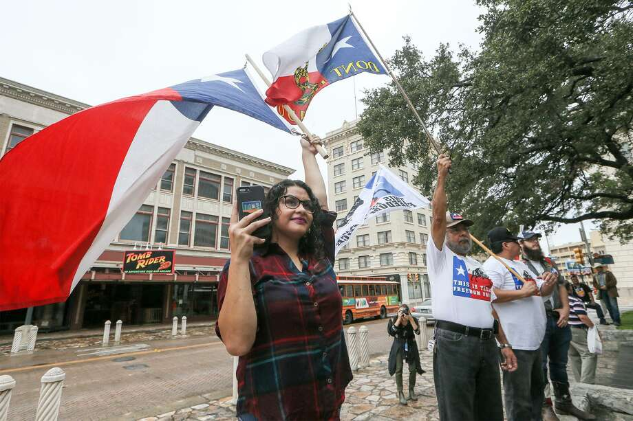Karina Gurrola, from left, Lupe Rivera, Ramon Garza and Paul Gescheidle hold flags as state Rep. Kyle Biedermann, R-Fredericksburg, holds a news conference Sept. 14 at the Cenotaph to oppose the proposed Alamo master plan and to urge officials to include the Texas Legislature in the negotiations going forward. Photo: Marvin Pfeiffer /Staff Photographer / Express-News 2018