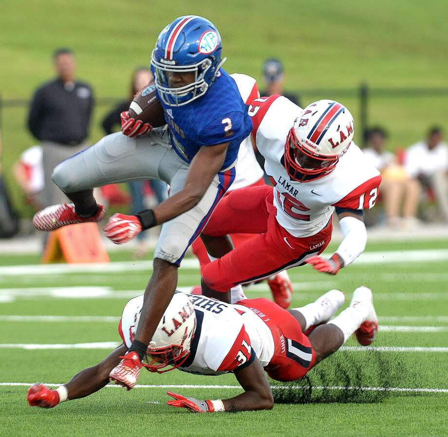 West Brook's Deonte Simpson leaps past the tackle attempt by Houston Lamar's Darius Shields (bottom) and Matthew Mabin during Friday's match-up at Beaumont Memorial Stadium.  Friday, September 14, 2018  Kim Brent/The Enterprise Photo: Kim Brent / The Enterprise / BEN