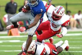 West Brook's Deonte Simpson leaps past the tackle attempt by Houston Lamar's Darius Shields (bottom) and Matthew Mabin during Friday's match-up at Beaumont Memorial Stadium. Friday, September 14, 2018 Kim Brent/The Enterprise