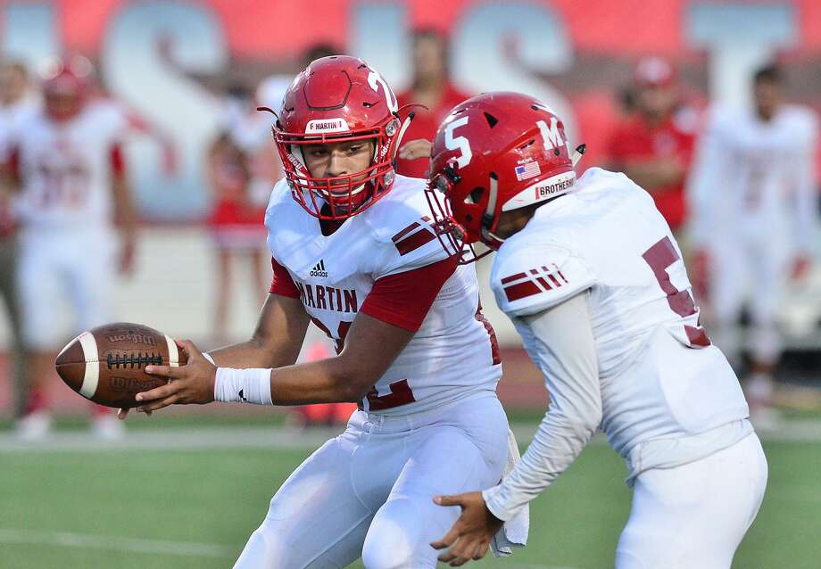 Quarterback Jose Castañeda prepares to handoff the ball to his running back Miguel Sanchez as the Martin Tigers and the Cigarroa Toros played at Shirley Field Friday, September 14, 2018. Photo: Cuate Santos /Laredo Morning Times / Laredo Morning Times