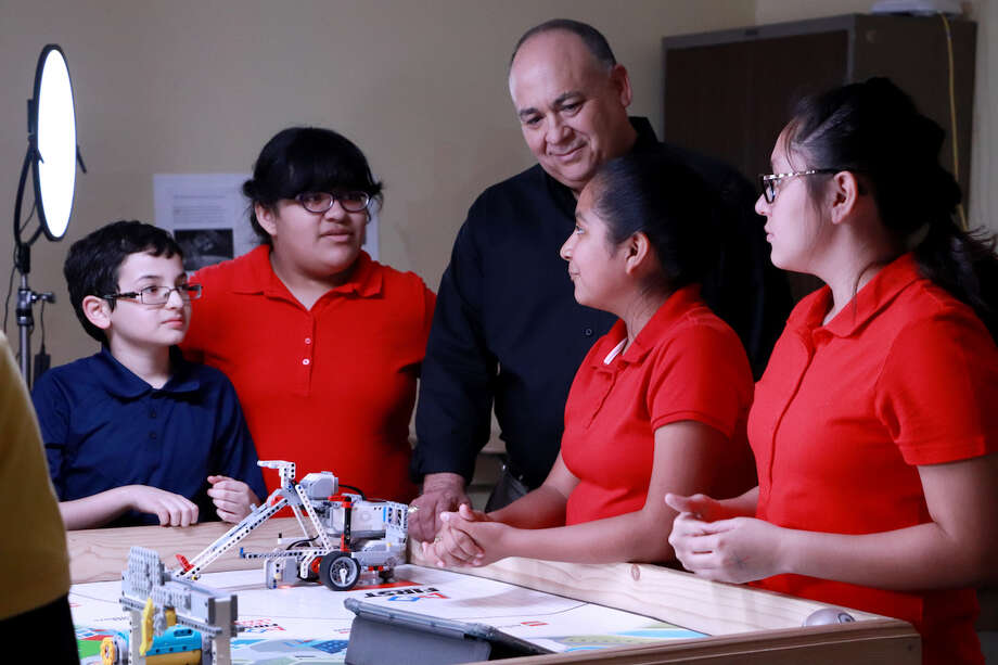 Four Cigarroa Middle School students are shown with Tony Arce, AEP manager, during filming. Photo: LISD/Courtesy