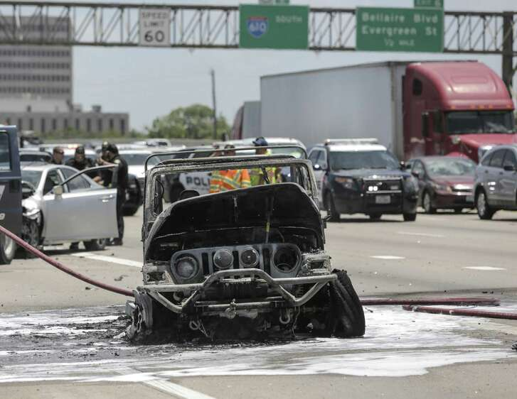 Members of Bellaire Fire Department work on a 1998 Jeep Wrangler that caught on fire after being rear-ended on Loop 610, backing up traffic in Bellaire.