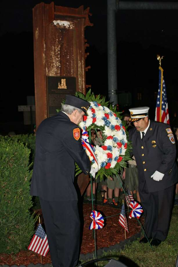 Glenville Volunteer Fire Company president Sandy Kornberg, at left, and Chief Michael Hoha place a memorial wreath by a piece of steel that was once part of the World Trade Center at the department's annual ceremony in Greenwich on Sept. 11. Photo: Contributed Photo / Greenwich Time Contributed