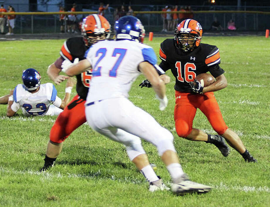 Gillespie's Dominik Taylor (right) cuts inside while Carlinville defender Jake Ambuel (27) takes on a Miners blocker during a Week 3 football game in the South Central Conference at Gillespie. The Miners were in Roxana on Friday and picked up their first victory with an overtime win over the Shells. Photo: Greg Shashack / The Telegraph