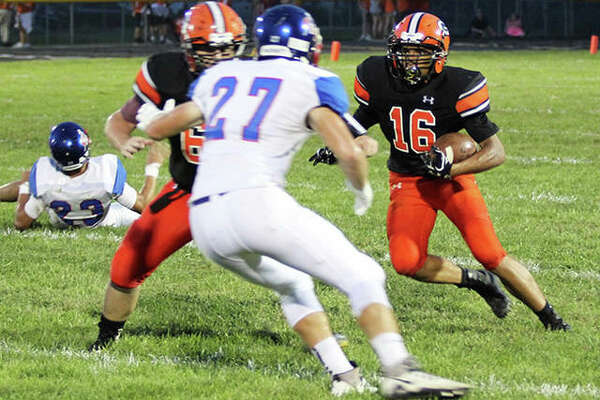 Gillespie's Dominik Taylor (right) cuts inside while Carlinville defender Jake Ambuel (27) takes on a Miners blocker during a Week 3 football game in the South Central Conference at Gillespie. The Miners were in Roxana on Friday and picked up their first victory with an overtime win over the Shells.