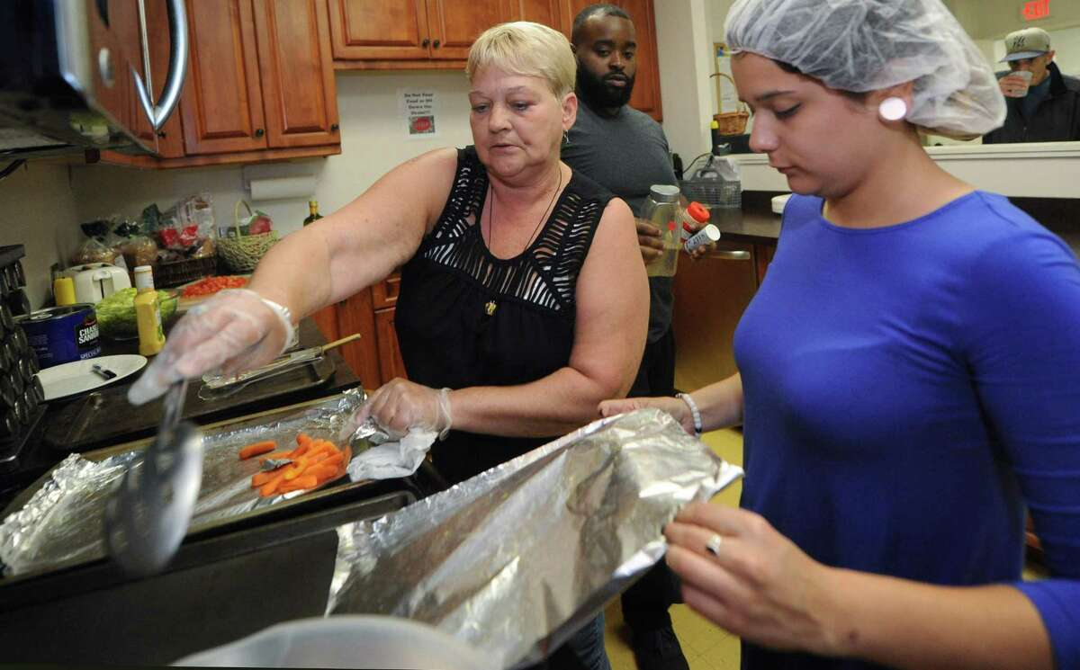 Keystone House client Dottie Greene helps staffers Jeffry Smith and Sereina Colon prepare lunch Thursday, September 6, 2018, at Keystone's Community Living Center on Main Avenue in Norwalk, Conn.