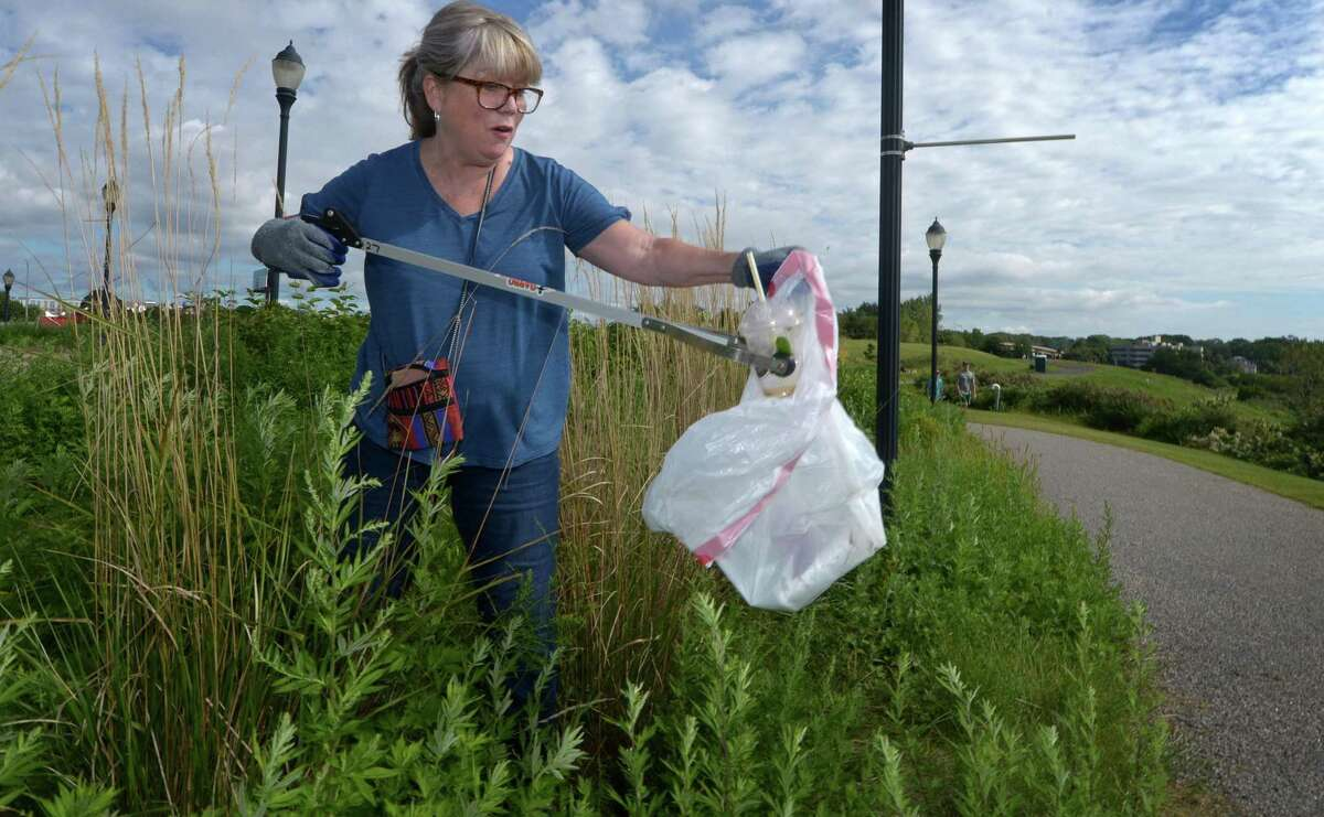 Volunteers including Norwalk resident Cathy Sasloe collect trash along Oyster Shell Parl Saturday, September 15, 2018, as part of the International Coastal Cleanup (ICC) 2018 in Norwalk, Conn. The volunteers weighed the collected, bagged trash, categorized it and will report it the Ocean Conservancy to help them track and eliminate ocean debris as part of the cleanup. Every September for more than 30 years, ICC has motivated over 11.5 million people from around the world to pick up over 210 million pounds of trash from nearly 390,000 miles of shoreline, according to Save the Sound. The cleanup is co-sponsored by NRWA, Woodcock Nature Center, Harbor Watch, Surfrider, Grace Farms, Keep Norwalk Beautiful and The Sheffield Sono.