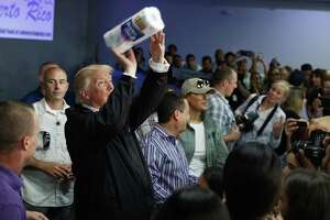President Donald Trump tosses paper towels into a crowd as he hands out supplies at Calvary Chapel, Tuesday, Oct. 3, 2017, in Guaynabo, Puerto Rico. Trump is in Puerto Rico to survey hurricane damage.