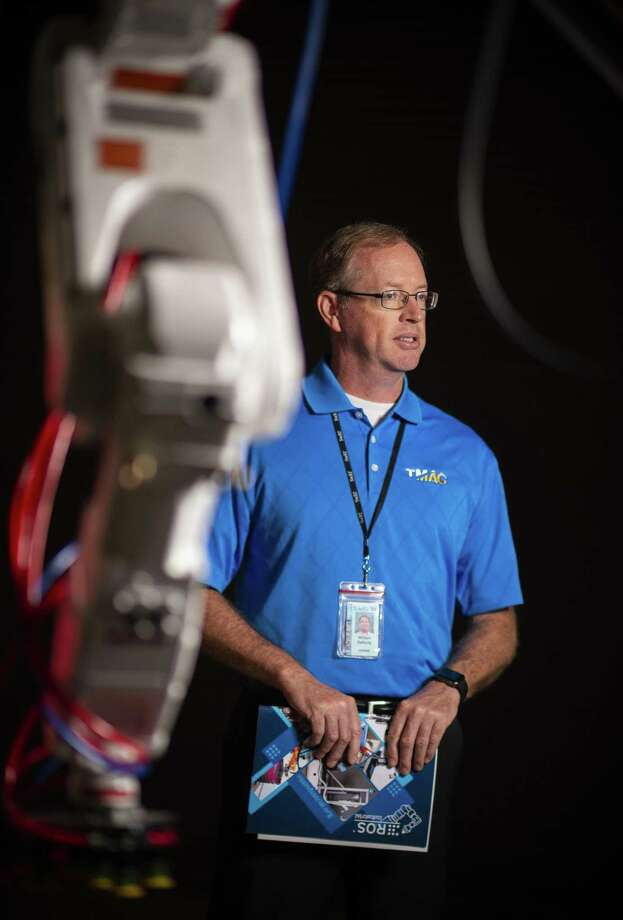 "Bill Rafferty, a regional director for the Texas Manufacturing Assistance Center, stands next to a collaborative robot at their facilities on Friday, September 7, 2018. The Southwest Research Institute recently announced the opening of a collaborative robotics lab designed to help manufacturers figure out how robots and humans can work together. The so-called ""cobots"" can safely perform tasks alongside humans. Photo: Carlos Javier Sanchez/pixelreflexmedia.com / Carlos Javier Sanchez